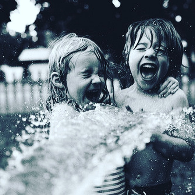 Young children laughing out loud while being splashed by water hose