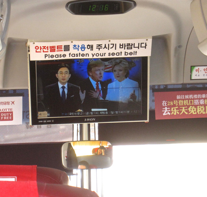 TV monitor on shuttle bus in Seoul, hours before the 3rd Clinton/Trump presidential debate, 2016 (ph