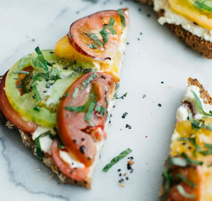 Take 2 slices of a hearty whole-grain bread, spread each slice with 1 tablespoon of homemade macadamia ricotta cheese, and sprinkle with shiso or basil, kosher salt, and fresh cracked pepper to taste. Add 1-2 hearty slices of fresh heirloom tomatoes (blotted with paper towel to remove excess liquid) and enjoy.