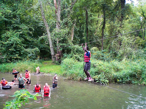 REACH youth crossing a river on a rope bridge