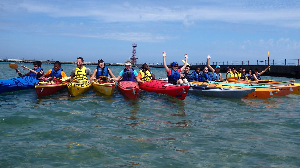 REACH participants and volunteers in a line of kayaks in Lake Michigan