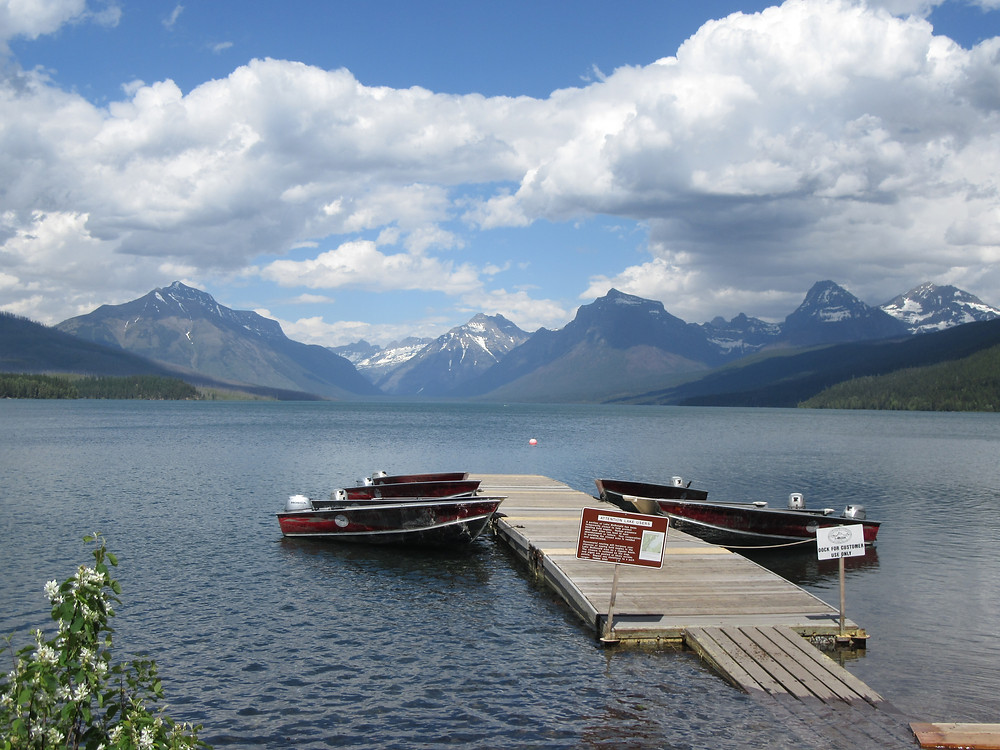Photo of a lake with boats in the foreground and snow capped mountains in the background