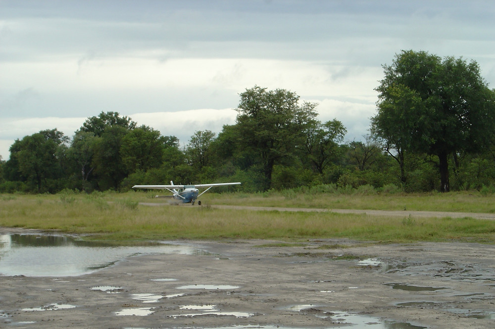 small aircraft landing on dirt airstrip