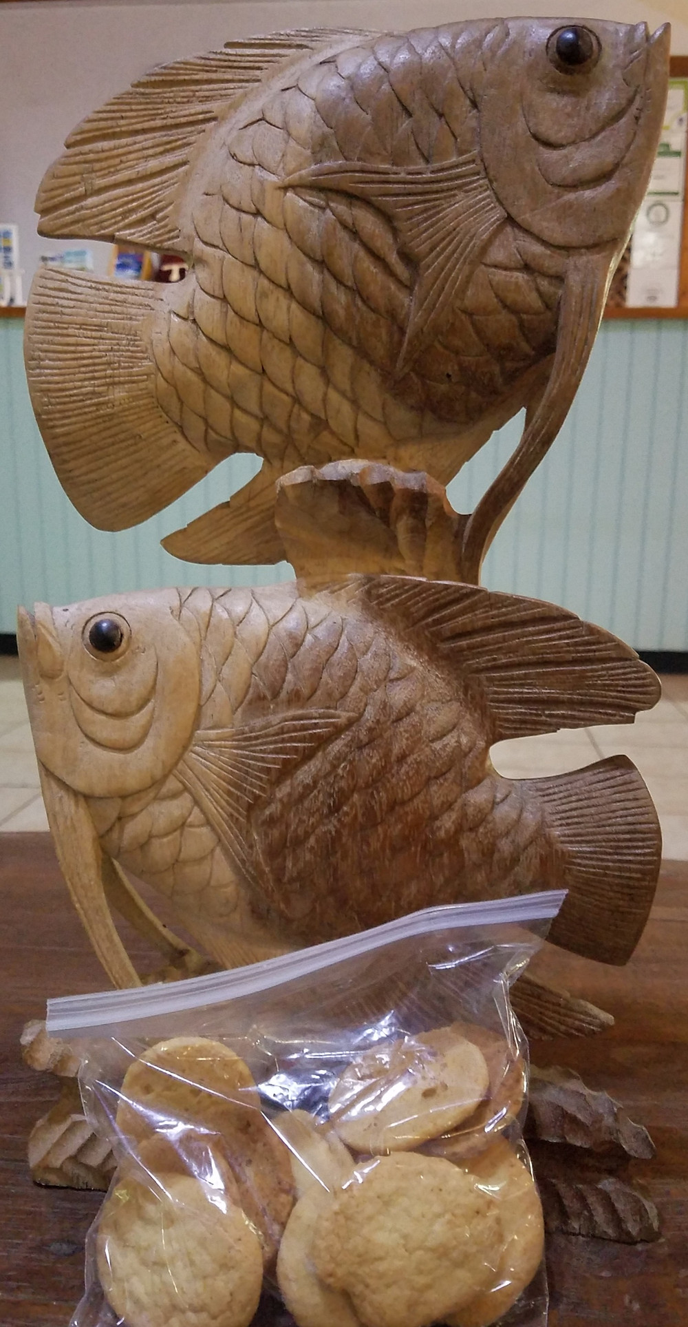 photo of wooden fish carving and bag of coconut cookies
