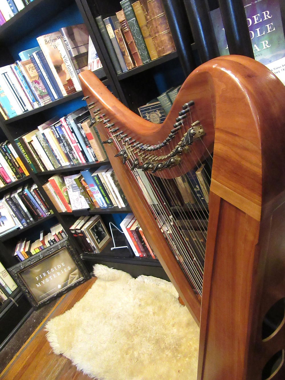harp in foreground with books on shelves in background