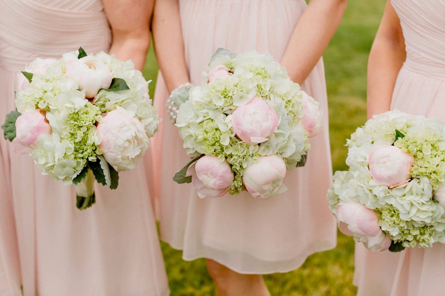 3 Bridesmaids in a row with bouquets