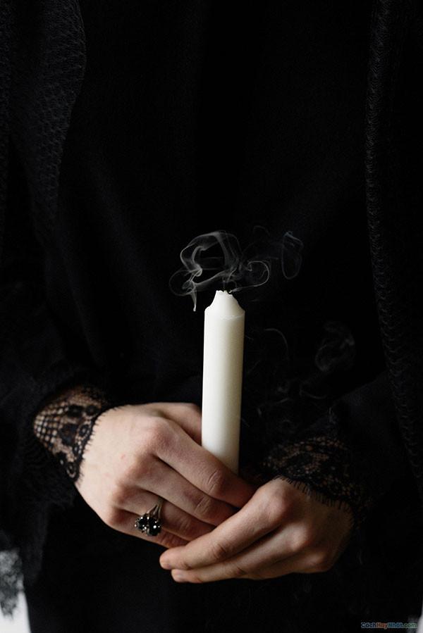 Ngọn nến màu trắng tắt trên tay người phụ nữ mặc quần áo đen