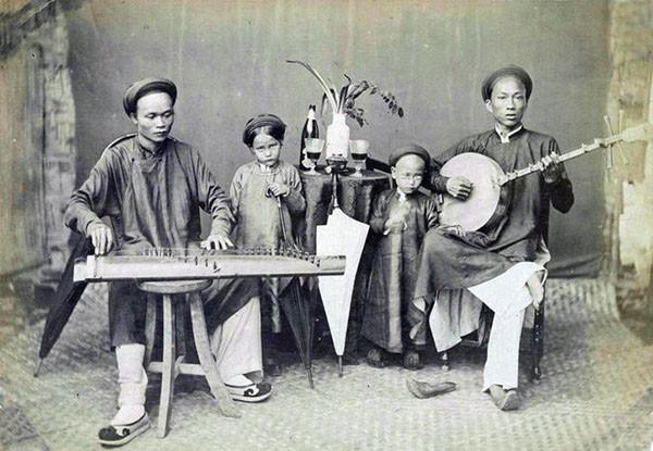 Các nhạc công biểu diễn với đàn tranh và đàn nguyệt. Rượu tây được bày trên chiếc bàn ở giữa.
