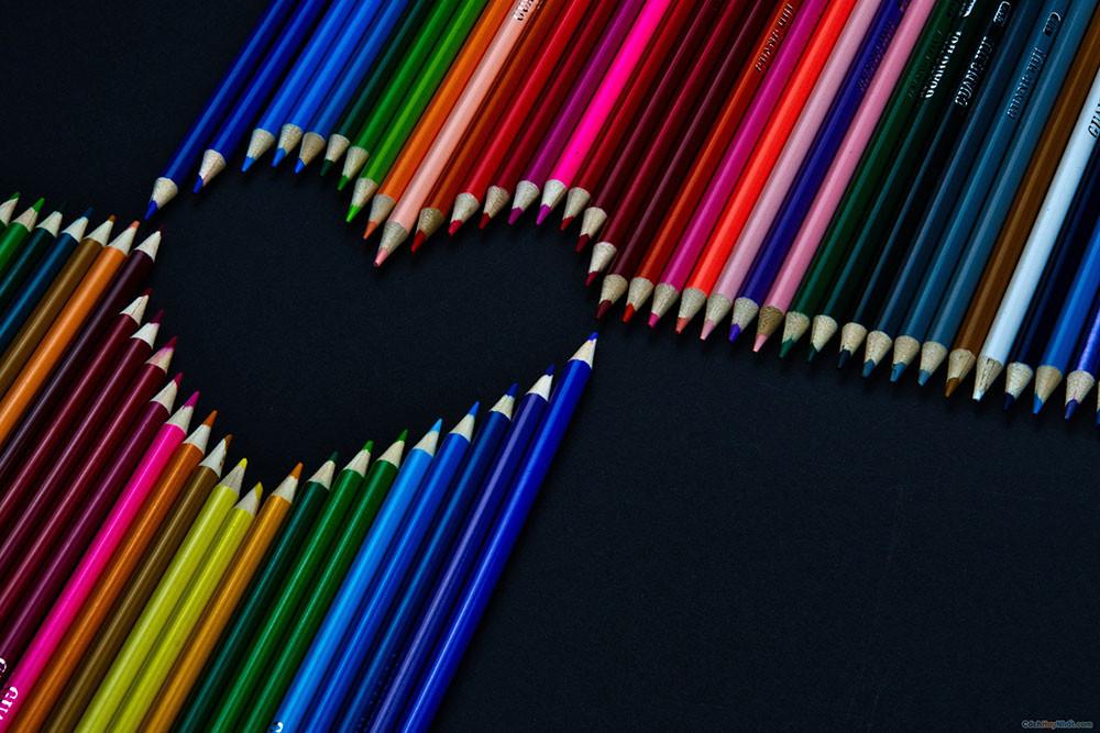 Bút chì nhiều màu xếp thành hình trái tim trên nền màu đen