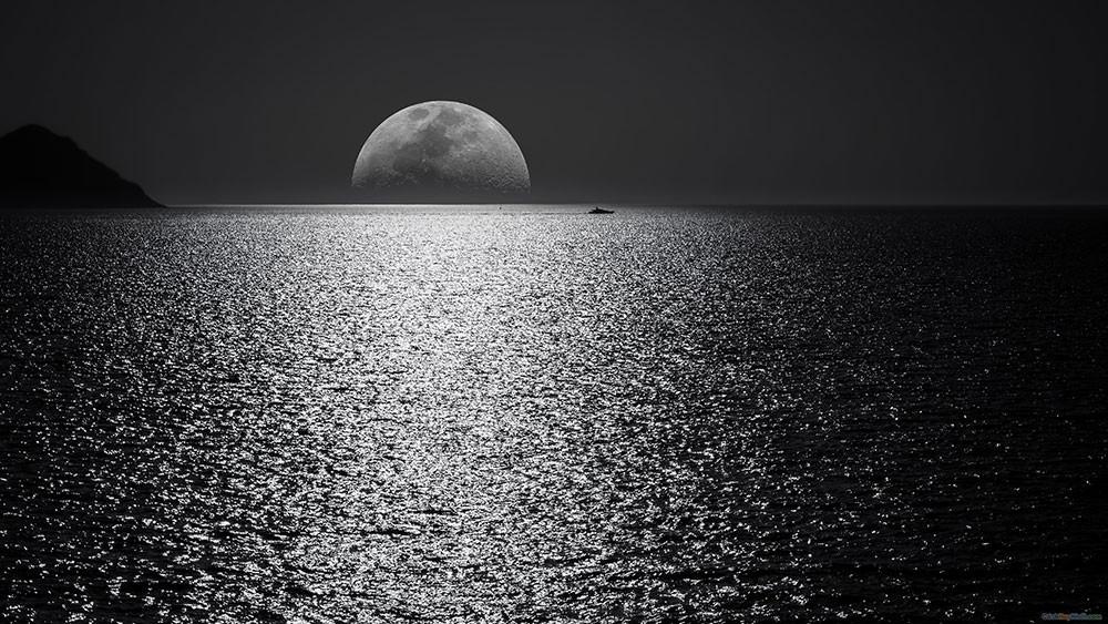 Mặt trăng và bầu trời đen trên mặt nước trong đêm