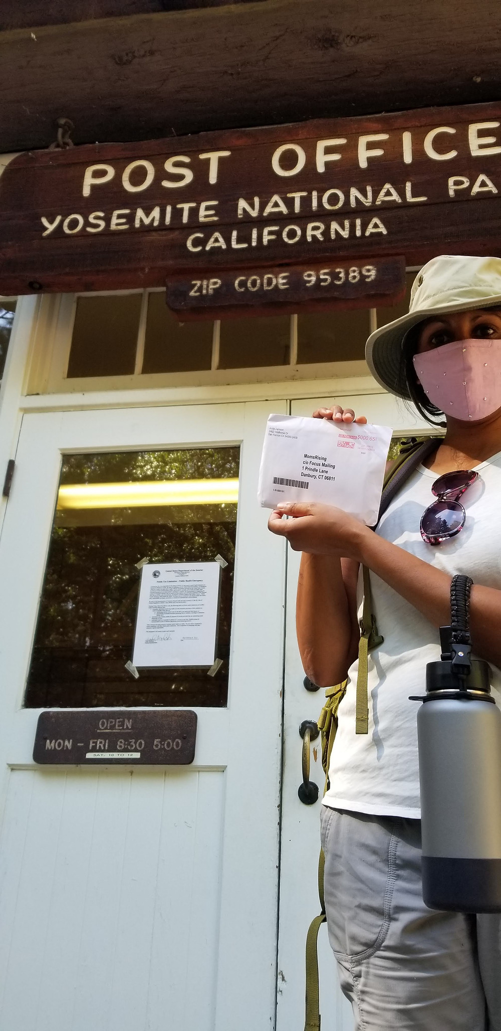 A person stands in front of the post office sign in Yosemite National Park, holding up an envelope and wearing a hat and a lavender mask.