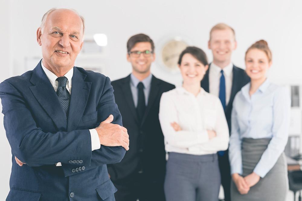 senior business man standing next to family