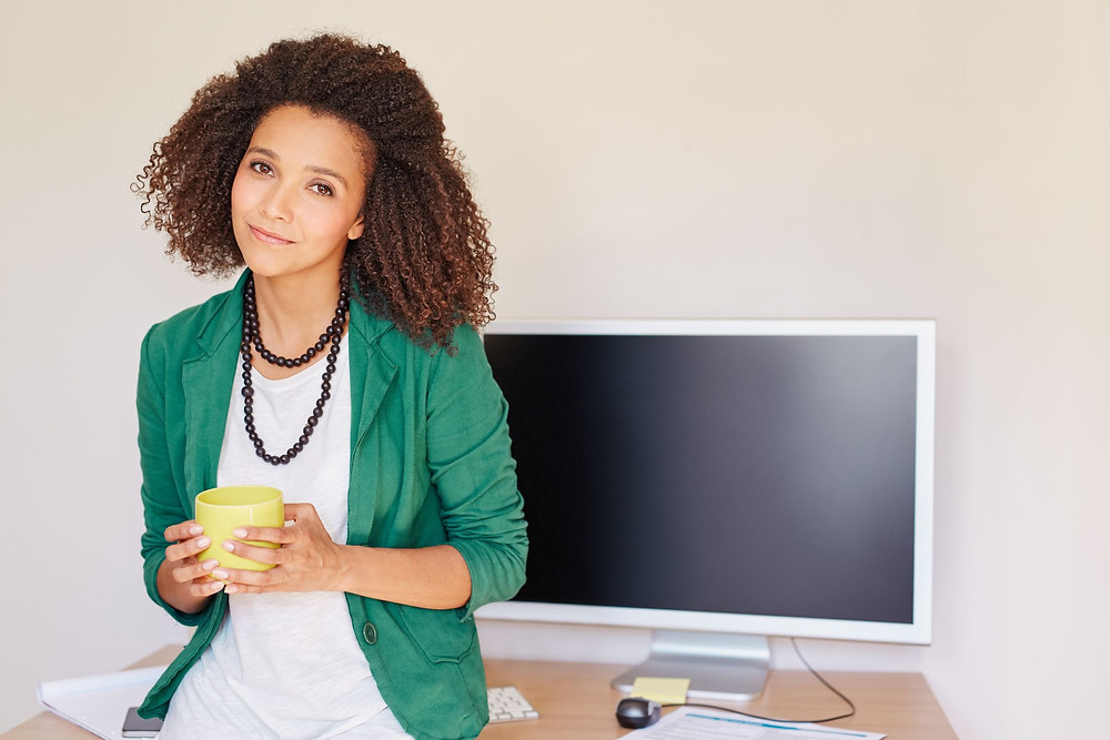 woman holding coffee next to monitor