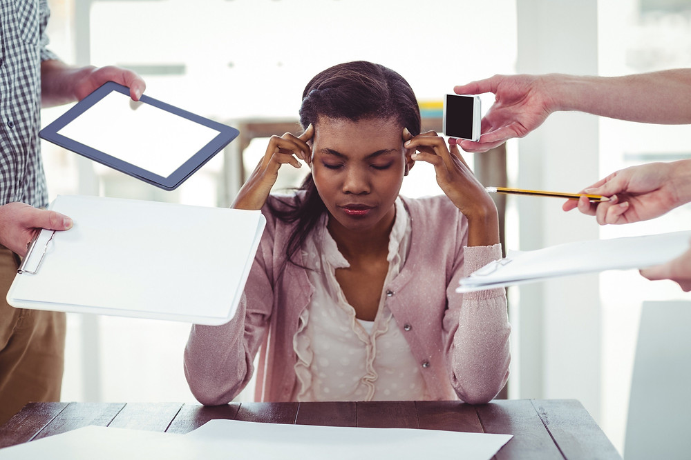 people trying to give overworked woman phone, pencil, and multiple documents