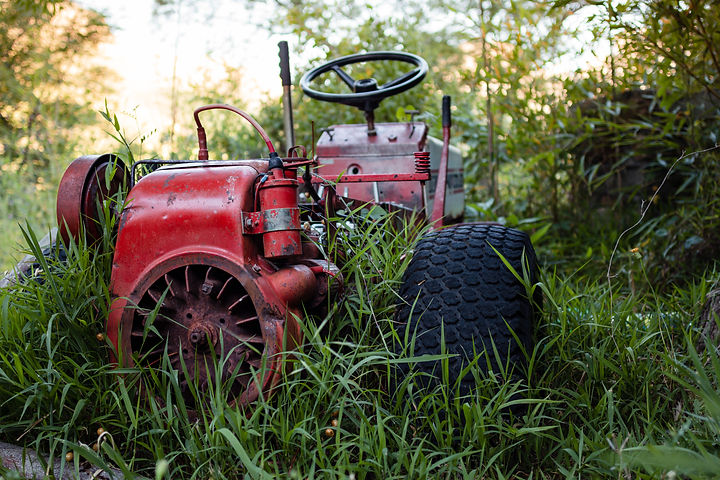 Small red tractor rusty and abandoned in
