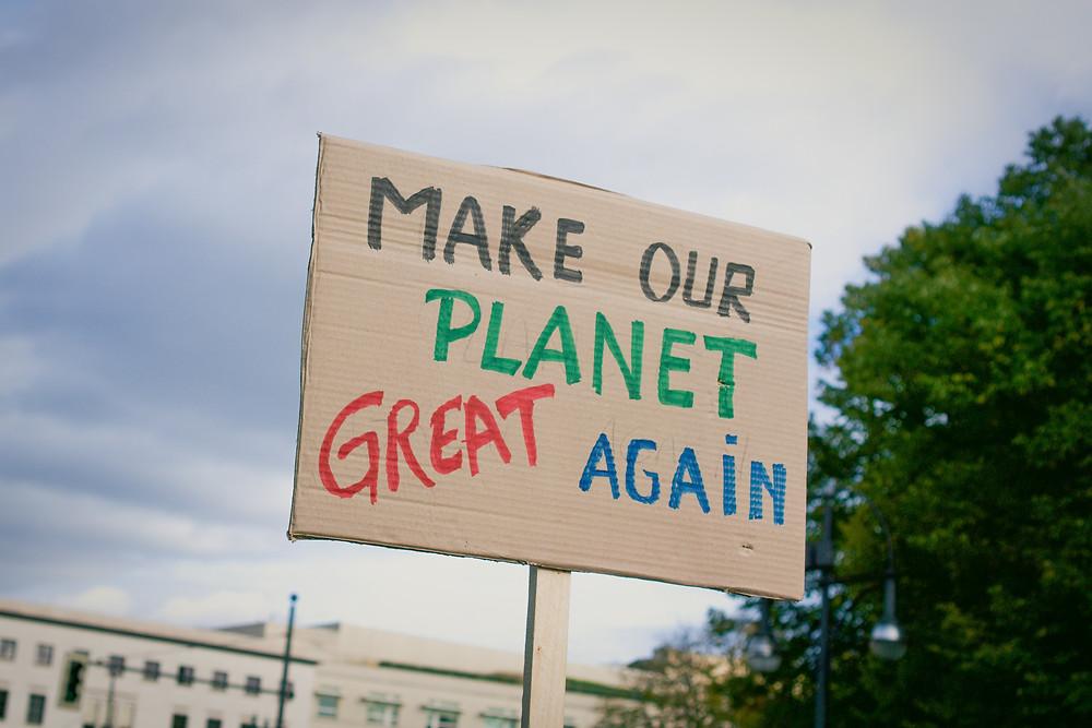 Placa de papelão escrita com as palavras make our planet great again