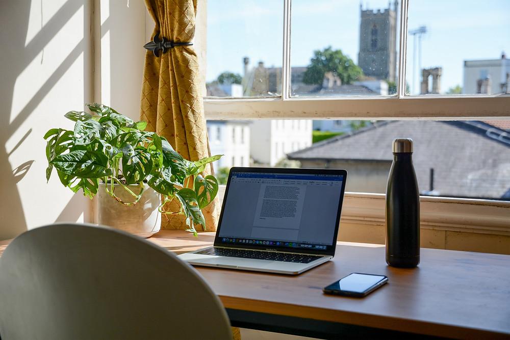 trabalho home office com computador, celular, mesa, garrafa de água, em frente à janela