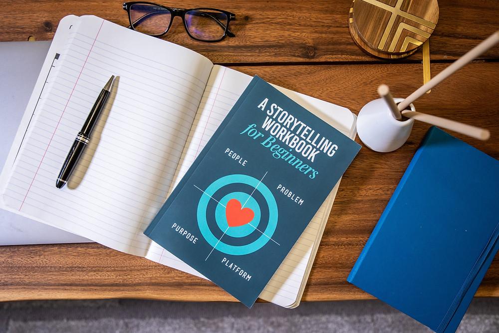 Sobre uma mesa um caderno, um livro, caneta e óculos