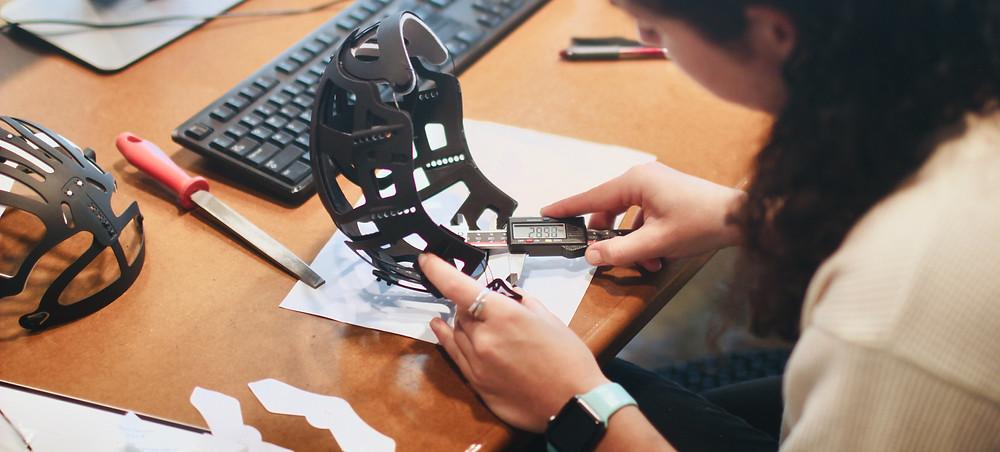 Mulher usa ferramenta para medir um protótipo de capacete