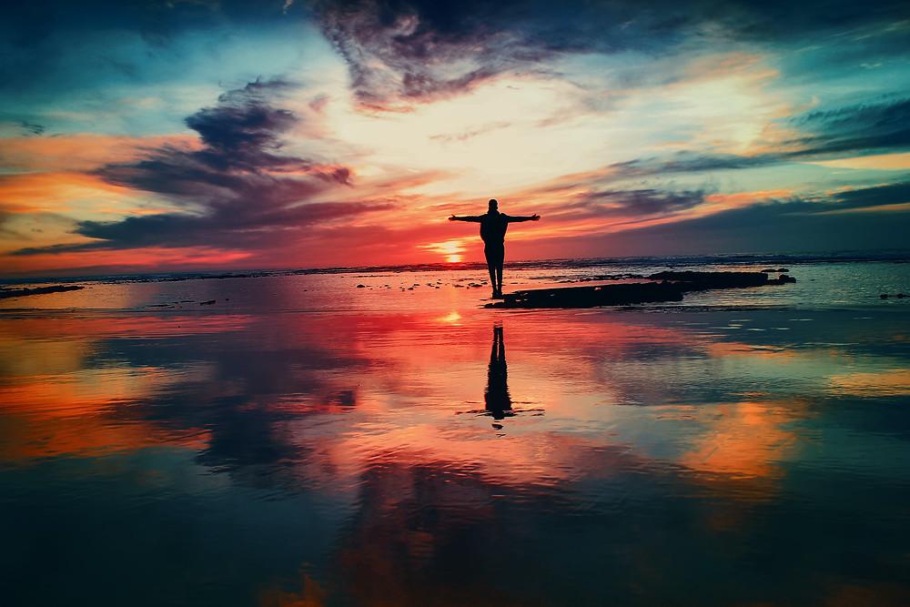 Imagem de céu colorido refletindo na água, com uma pessoas de braços abertos no meio da imagem