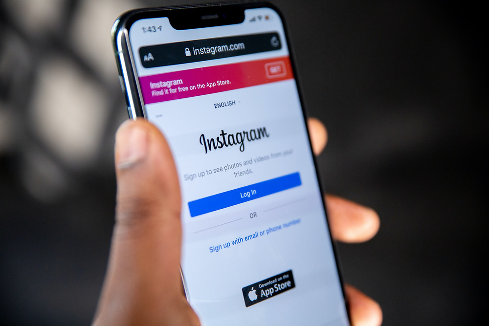 Uma mão segura o celular com a imagem do instagram na tela