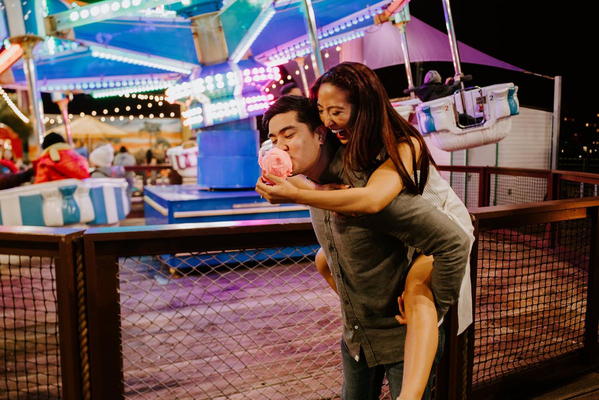 Santa Monica Pier carnival fair engagement cotton candy piggy back ride pose asian couple love