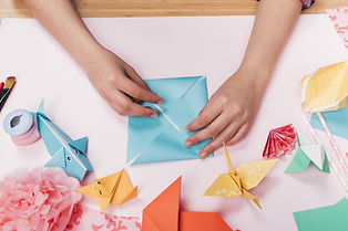 top-view-of-woman-hand-making-origami-craft-over-table-min.jpg