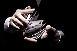 magician-shuffling-the-cards-in-cool-way-under-the-spotlight-min.jpg