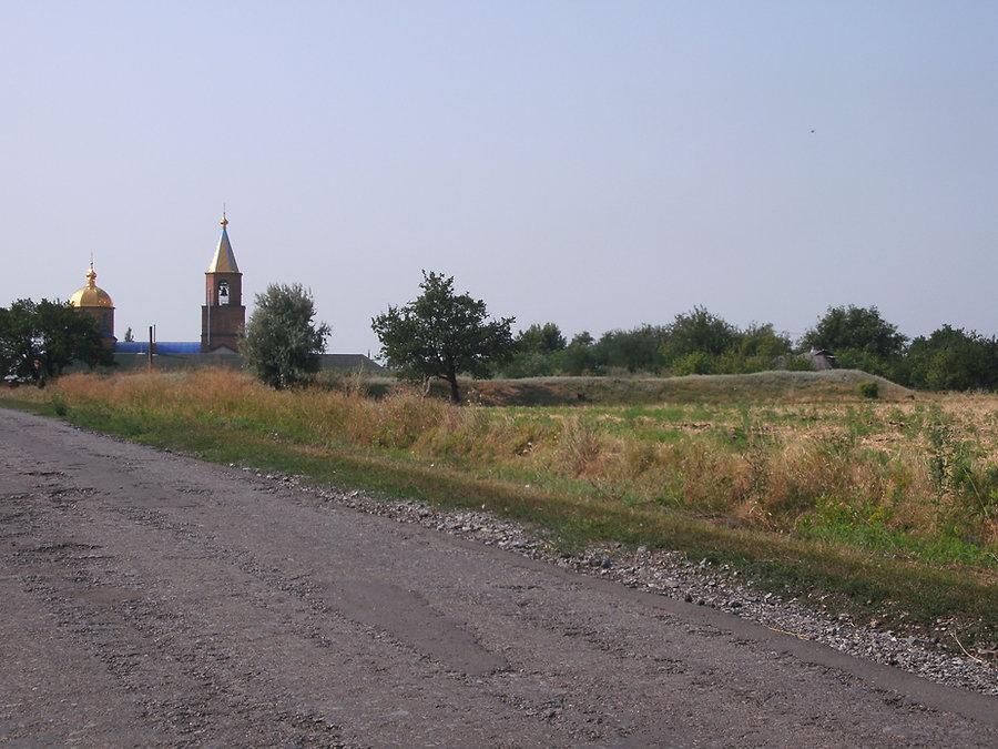Остатки отвала породы одной из шахт рудника Ларина на фоне храма
