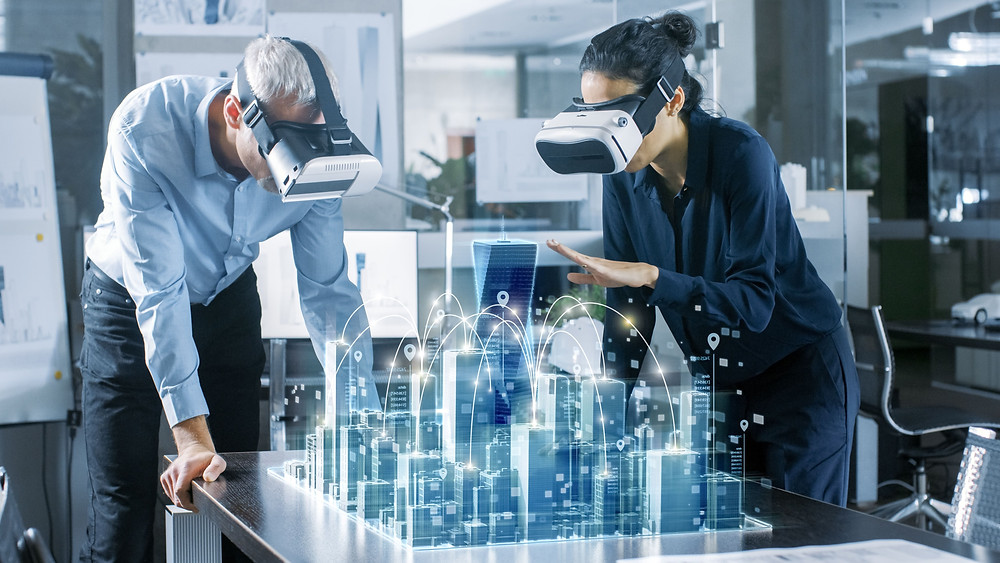 Two person looking a 3D model of a city using virtual reality glasses.