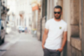 Man leaning against a wall wearing an organic white Mammoth Logo T-shirt from Ninefoot