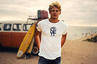 Young man standing in front of his van and surfboards wearing a white NFT T-shirt from Ninefoot