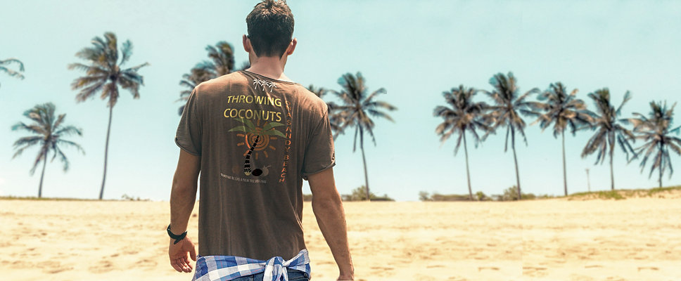 Man walking on the beach wearing an organic brown Be like a palm tree T-shirt from Ninefoot