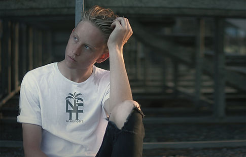 Handsome young man wearing a white NFT T-shirt from Ninefoot