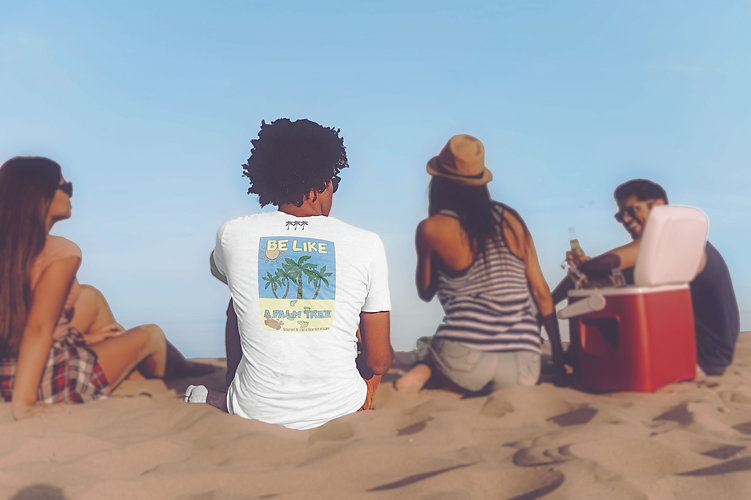 Young Afro American Man wearing an organic white Be like a palm tree T-shirt from Ninefoot and enjoying beach life with his friends