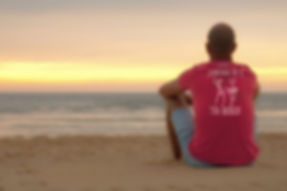 Man sitting on the beach wearing an organic spiced coral red Be like a palm tree T-shirt from Ninefoot