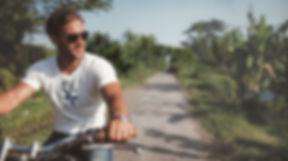 Man riding bike wearing white NFT T-shirt from Ninefoot