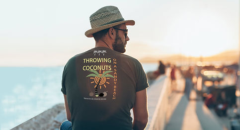 Handsome man sitting on a wall near the sea wearing his hat and organic brown Be like a palm tree T-shirt from Ninefoot