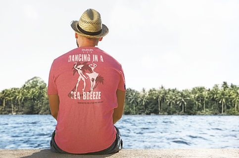 Man sitting on a wall wearing an organic pink Be like a palm tree T-shirt from Ninefoot