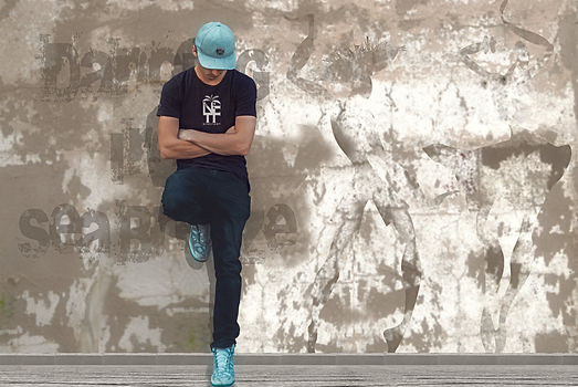 Young man leaning against a wall wearing a blue NFT T-shirt from Ninefoot