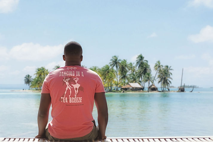 Afro American Man sitting on a dock wearing an organic spiced coral red Be like a palm tree T-shirt from Ninefoot