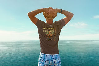 Man looking over the ocean wearing his hat and organic brown Be like a palm tree T-shirt from Ninefoot