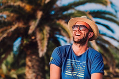 Smiling man enjoying the sun wearing his hat and vintage blue Be like a palm tree T-shirt from Ninefoot