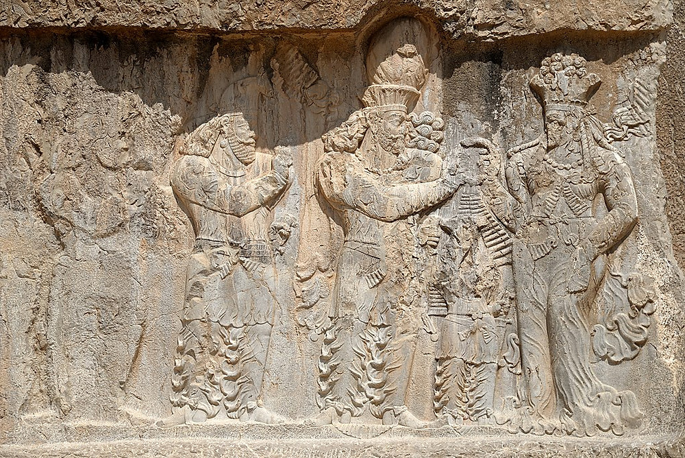 An ancient Persian stone relief depicting four ahura, including Mithra and Anahita, discussing something while wearing crowns