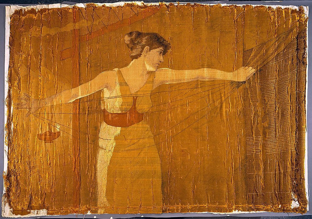 A fabric painting depicting a woman with brunette hair wearing a yellow dress stretching her arms out as she pulls threads from a hanging cloth; behind her, a lamp lights the scene gold, showing that it is nighttime