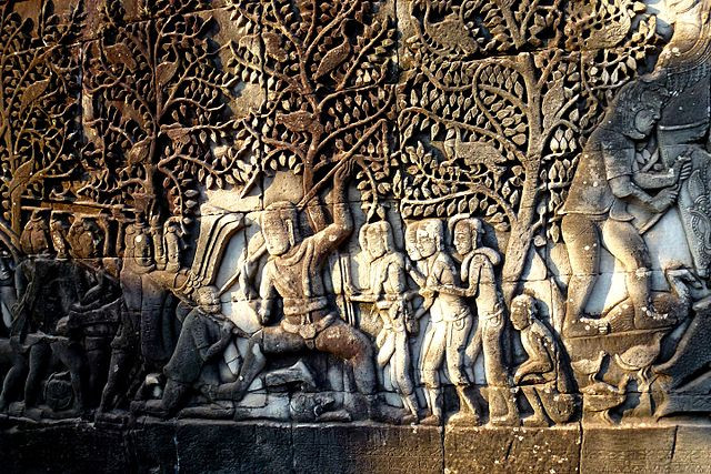 An ancient stone relief from Angkor Wat depicting a battle between deva and asura beneath the canopy of a forest