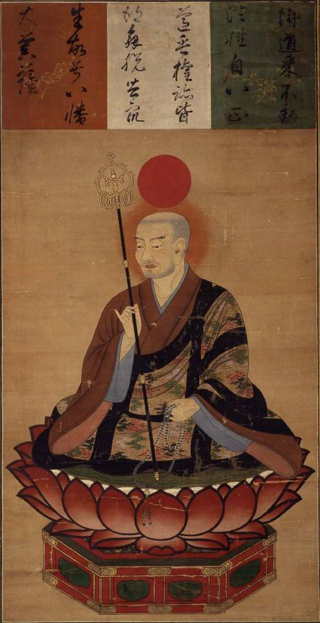 An ancient Japanese painting of the god Hachiman, shown here with a sceptre and the red sun disc above his head, wearing opulent robes and holding a length of Buddhist prayer beads, seated on a lotus flower.