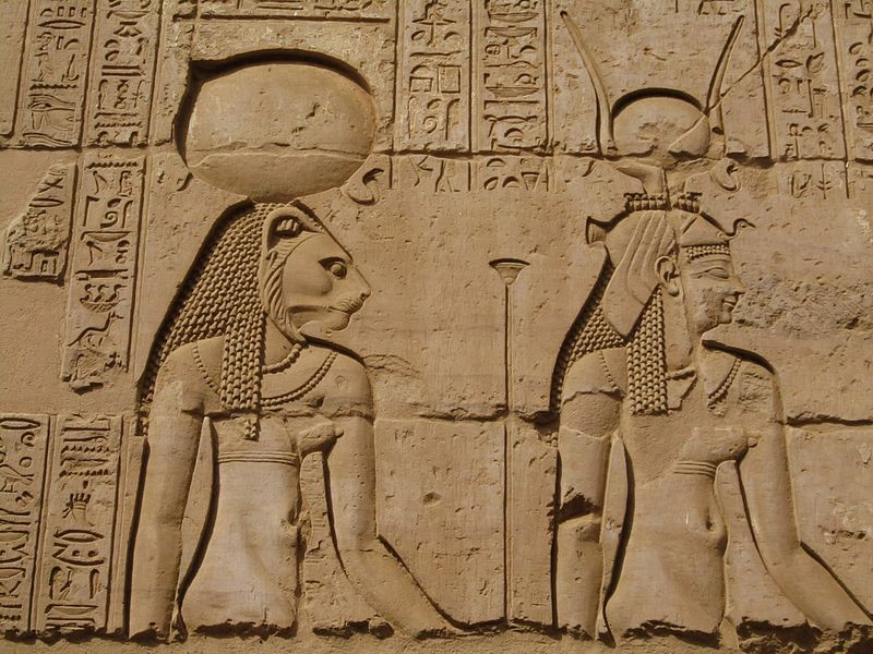 An ancient Egyptian wall relief depicting the lion-headed goddess Sekhmet to the left with a sun disc on her head, and the goddess Hathor on the right with cow horns and a vulture headdress