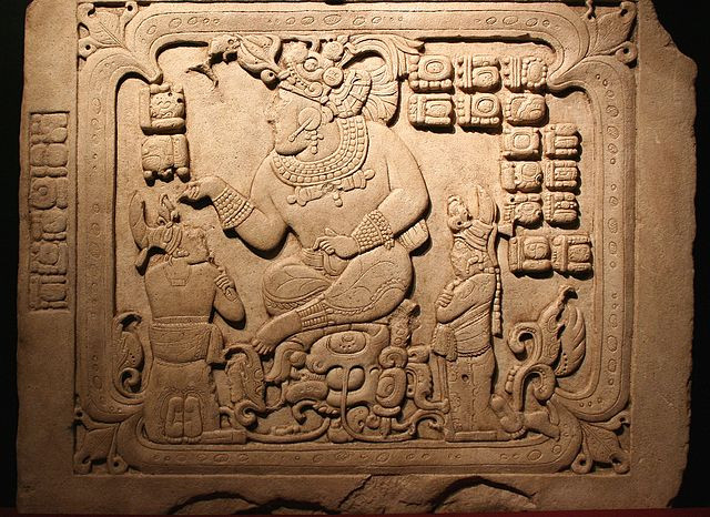 An ancient Maya stone relief of the ahau T'ah 'ak' Cha'an sitting enthroned above two much smaller supplicants