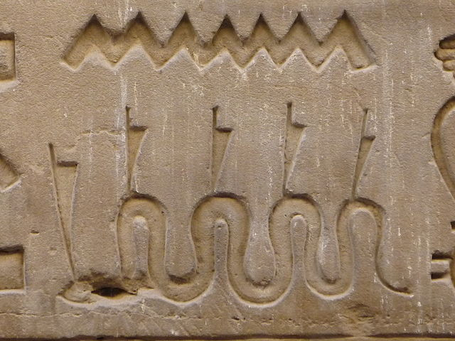 An ancient stone relief of the serpent Apep with crowns on each of its coils